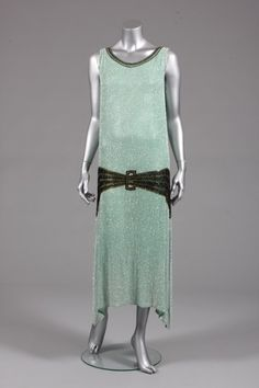 A pale green beaded evening gown, circa 1929, the muslin ground covered with a shimmer of pearlised bugle beads with black and gold bead belt buckle medallion, hem falls in points at each side   Kerry Taylor Auctions
