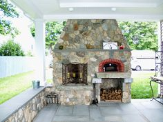 A wood fired #BrickOven Pizzeria on a covered patio in a BROM Builders, CT home!
