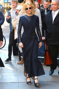 Sienna Miller gets in the layer game with a shirt under her navy dress, paired with black sandals.