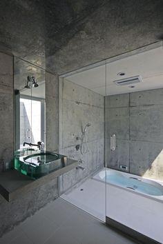 #reforma #baño (presupuestON.com) con lavabo de vidrio sobre encimera de hormigón, zona de baño con ducha y bañera bajo suelo.