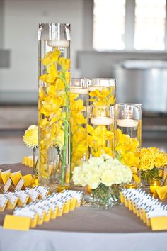 Yellow orchids + white floating candles in tall glass cylinders.