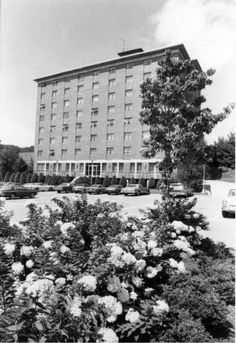 This image shows the west side of Cannon Residence Hall in August 1977. Also shown are cars in the parking lot and late summer foliage in the foreground. Cannon Hall was a women's dormitory, constructed in 1968, and was part of the Eastridge Community, which also includes Lovill, White, Doughton, and Hoey Halls. It later became a co-educational dormitory.