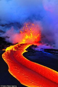 River of lava boils down the mountainside into the sea in Hawaii.