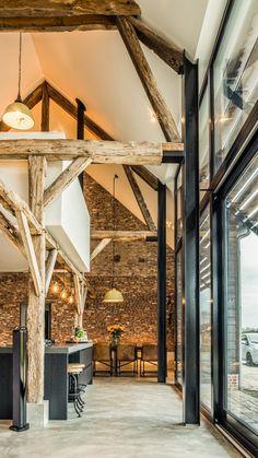 Inpassing van het witte blok met keuken, boekenkast en studie tussen de oude houten balkenstructuur.