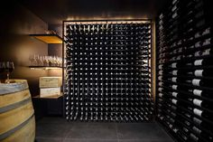 Contemporary basement wine cellar is filled with a large block wine rack accented with custom lighting adjacent to a wall lined with a floor to ceiling wine rack.
