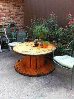 Discarded electrical cable spool repurposed as an outdoor table. Stain and seal. Voila!