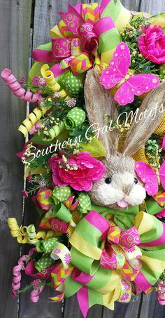 The Easter Bunny is here and Ready for Spring! This bright and cheerful Spring Easter Swag will look wonderful for your Spring/Easter decor. The Spring Easter bunny swag measures 36  x 24 x 10. The swag is full and bountiful. The swag was designed around the beautiful and bright tricolor ribbon (lime green, bright yellow, fuchsia pink). A large raffia bunny centers the wreath design. The swag is made of multiple deco mesh. The swag has been accented with multiple ribbon bows placed about...