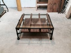 A modern industrial coffee table made of black steel pipe, walnut wood slats, and 1/2 thick tempered glass, with a shelf below.    The