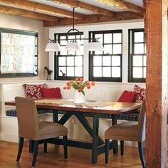 """An oak trestle table with a salvaged longleaf pine top was built to fit a nook along a bank of windows. Tom made sure the banquette's seat extended past the base so that people can tuck their legs beneath it. """"Otherwise, you'd step on each others' feet under the table,"""" he says. Another clever trick: adding forced-air supply vents in the toekick and along the cap molding to keep diners toasty."""