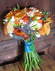 Orange calla lilies, white and orange dahlias, ranunculus, freesia, crocosmia, thistle and delphinium bouquet