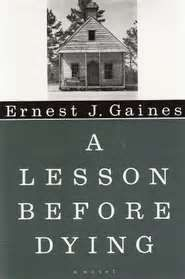 A Lesson Before Dying is set in a small Cajun community in the late 1940s.  Jefferson, a young black man, is an unwitting party to a liquor store shoot out in which 3 men are killed; the only survivor, he is convicted and sentenced to death.  Grant Wiggins has returned to the plantation school to teach.  As he struggles with his decision whether to stay or leave, his aunt & Jefferson's godmother persuade him to visit Jefferson in his cell before his death.