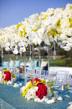 Tall floral centerpieces that line the middle of long reception tables allow guests to easily converse.