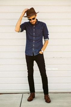 Men's Brown Wool Hat, Black Sunglasses, Black Jeans, Brown Leather Derby Shoes, Dark Brown Watch, and Navy Denim Shirt
