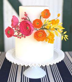 White wedding cake with pink, orange + yellow sugar flowers