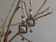 Square bead frames with a Swarovski pearl is the focal point of these earrings. The silver plated bead frame is accompanied with Swarovski $20.00