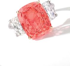 Padparadscha Sapphire and Diamond Ring. Set with a cushion-shaped padparadscha sapphire weighing 8.01 carats, flanked on each side by a cushion-shaped and old-mine-cut diamonds weighing 1.01 and 1.00 carat respectively, mounted in 18 karat white and pink gold. Ring size: 6