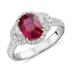 An extraordinary, one-of-a-kind ring showcasing a vibrant oval faceted ruby accented by two brilliant half moon diamonds.
