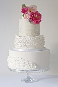 White ruffle wedding cake with silver details and bright pink sugar flowers @CakesBySophie