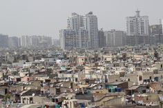 Houses, Apartments ... Antennas - A photo shows how Indian societies are formed together where the low (slum) class and upper (middle) class lives together in harmony.  Though there is one commonality - Dish antennas!