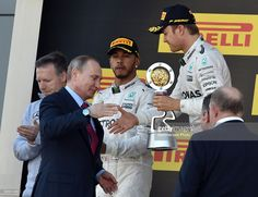 Nico Rosberg of Germany and Mercedes GP (R) collects his winners trophy from Russian President Vladimir Putin (L) during the Formula One Grand Prix of Russia at Sochi Autodrom on May 1, 2016 in Sochi, Russia.