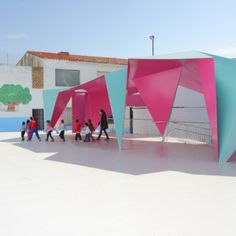 Thin sheets of brightly painted steel have been folded to create this origami-inspired canopy, designed to shelter a school playground in an Andalusian village