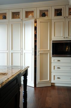 Gorgeous kitchen with floor to ceiling kitchen cabinets and walk-in pantry hidden behind white cabinet doors.