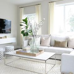Beautiful living room features a white sectional lined with pale pink velvet pillows as well as yellow and gray ikat pillows in Bansuri Fabric paired with a white marble top box frame coffee table and white trellis stools atop a cream diamond pattern rug. Living Room White, Beautiful Living Rooms, White Rooms, Living Room Grey, Rugs In Living Room, Living Room Furniture, Living Room Designs, Living Room Decor, White Sectional