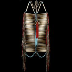 """Inspirational recreation of a 1870-s Lakota warrior bone hair pipe breastplate based on the existing original and my knowledge of a wide range of Lakota style breastplates. Comprises hand selected 4"""" genuine bone hairpipe, deer leather fringes and ties, brass beads, small gear-wheels of German silver, saddle leather spacers.  Источник: http://4colors.ru/nam2027.html © Галерея индейского искусства 4Colors"""