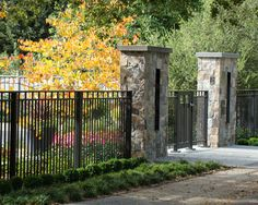 stone entrance gate columns with iron fencing. nice details. I like the light panels in the stone columns - Randy Thueme Design Inc. - Landscape Architecture