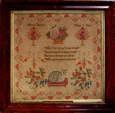 A framed sampler signed Mary Thornton aged 9. Poem, cat on cushion, flowers birds, surrounded by floral border.