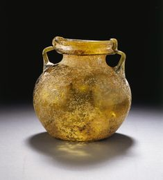 A LARGE ROMAN GLASS JAR   circa 3rd-4th century a.d.   Transparent gold in color, free-blown, the globular body on a concave base, with a short neck, flared rim and vertical lip, with twin pale green handle