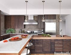 Pelham Pendant lights from Hudson Valley Lighting hang above the prep area of the island. The iron backs of Bistro Swivel Chairs fold down to become stools.   - HouseBeautiful.com