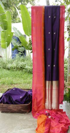 This violet coloured Benares silk has small gold zari bhuttas sparsely placed all over the sari. The border has a pink outer band and then an orange band with gold zari work all across. The pallu i...