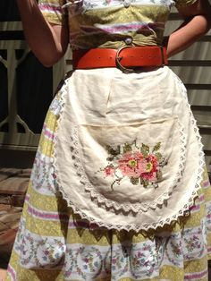 Half apron with hand embroidered pocket.