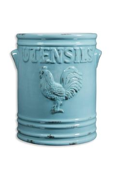 "This rooster utensil crock is made of ceramic and is a distressed aqua color. It features a raised rooster with the word ""utensils"" on the front and back. It measures approximately 5 1/2"" wide and 7"" tall.  Rooster Utensil Holder-Aqua by Home Essentials. Home & Gifts - Home Decor - Dining - Table Accessories Home & Gifts - Home Decor - Dining - Kitchen Tools New York"