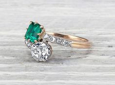 Antique Edwardian 'toi et moi' bypass ring made in platinum and gold featuring an EGL certified approximately .61 carat square cut natural emerald and approximately .86 carat J-K color SI1clarity old