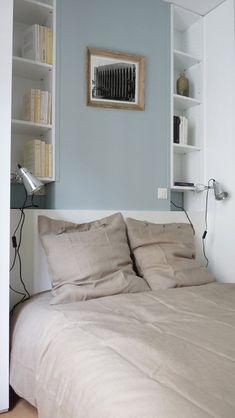 Le lit s'appuie contre la colonne de la cheminée camouflée dans un coffrage peint en bleu ciel. De part et d'autre, les niches avec étagères exploitent les renfoncements existants pour former deux petites bibliothèques symétriques.