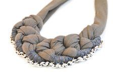 Leg Dich in Ketten. Elegant ausgefallenes Collier aus dunkelgrauem Jerseyband,grauglänzendem Häkelgarn und silberfarbener Gliederkette, gehalten vo