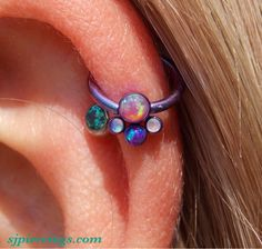 Titanium captive ring anodized blurple with an awesome clusters with a bubblegum pink opal, purple opal, and two light purple opals ^.^ so fancy!!! And all from Anatometal!! Ugh, stupid tumblr reduced quality on this picture. -.- www.sjpiercings.com Facebook.com/allstartattoosa
