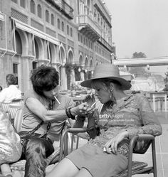 English musician Keith Richards litghting a cigarette to Anita Pallenberg, sitting outside the Excelsior Hotel, Lido, Venice, 1967.