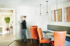 Pops of orange are a fun accent at this apartment clubhouse banquette seating area.