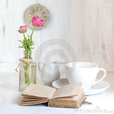 Two pink flowers ranunculus and old opening book