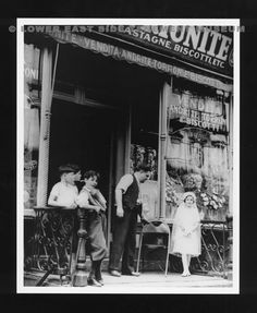 "Children stand outside of an Italian grocery on the Lower East Side in the 1930s. Girl is wearing a communion dress. Photograph was a part of the ""One Third of a Nation: The WPA Photographs of Arnold Eagle"" November 1988 exhibit at the Lower East Side Tenement Museum, 97 Orchard Street. (New York, 1935)"