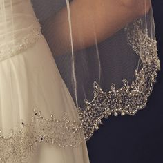 A breathtaking display of faux pearls, bugle beads, crystals and intricate threading neatly articulates this scalloping edge veil with shimmering beauty! Dainty flower accents add the perfect finishin