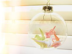 Origami cranes inside clear Christmas ornaments.