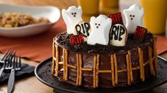 """Hosting a Halloween party? This spooky layer cake, topped with ghost-shaped marshmallows and pretzel """"fence,"""" is bound to knock the socks off your guests. To make nut free, skip the mini chocolate bars; minis usually have a nut allergy warning. Halloween Cakes, Halloween Treats, Halloween Party, Halloween Ghosts, Halloween Peeps, Spooky Treats, Halloween Foods, Halloween Recipe, Halloween 2014"""