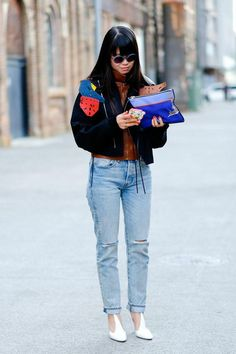Amazing Fashion Week Australia 2015 Street Style - black suede coat layered over a brown leather vest, worn with light washed + distressed baggy jeans, and an electric blue zip clutch