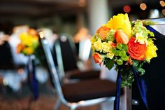 Wedding ceremony aisle decor: succulents, orange and yellow flowers with with tulips, roses, euphorbia, mini daffodils, and viburnum.