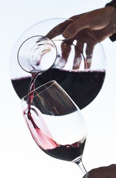 Waiter pouring the wine in a glass with a carafe - luxury wine accessories at https://www.mimisfifis.com