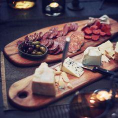 Zwei Schneidebretter aus massivem Akazienholz, darauf sind verschiedene Käsesorten und Wurst arrangiert.